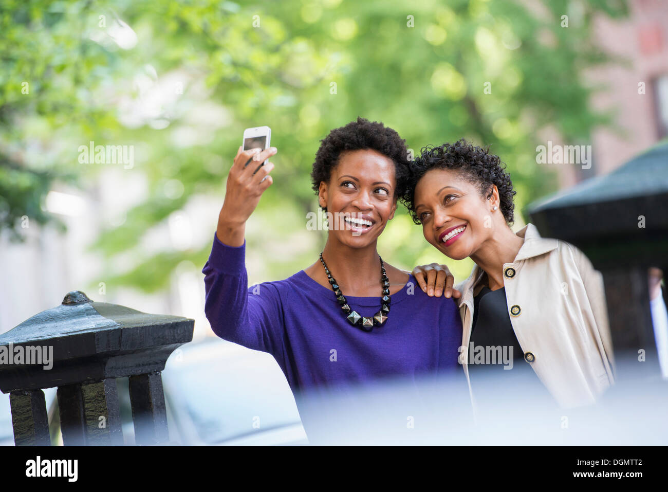 City life. Two women sitting on a park bench, side by side. Posing for a photograph with a smart phone. - Stock Image