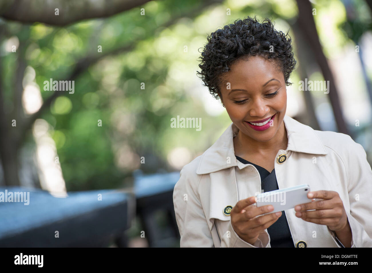 City. A woman outdoors in the park, checking her smart phone. - Stock Image