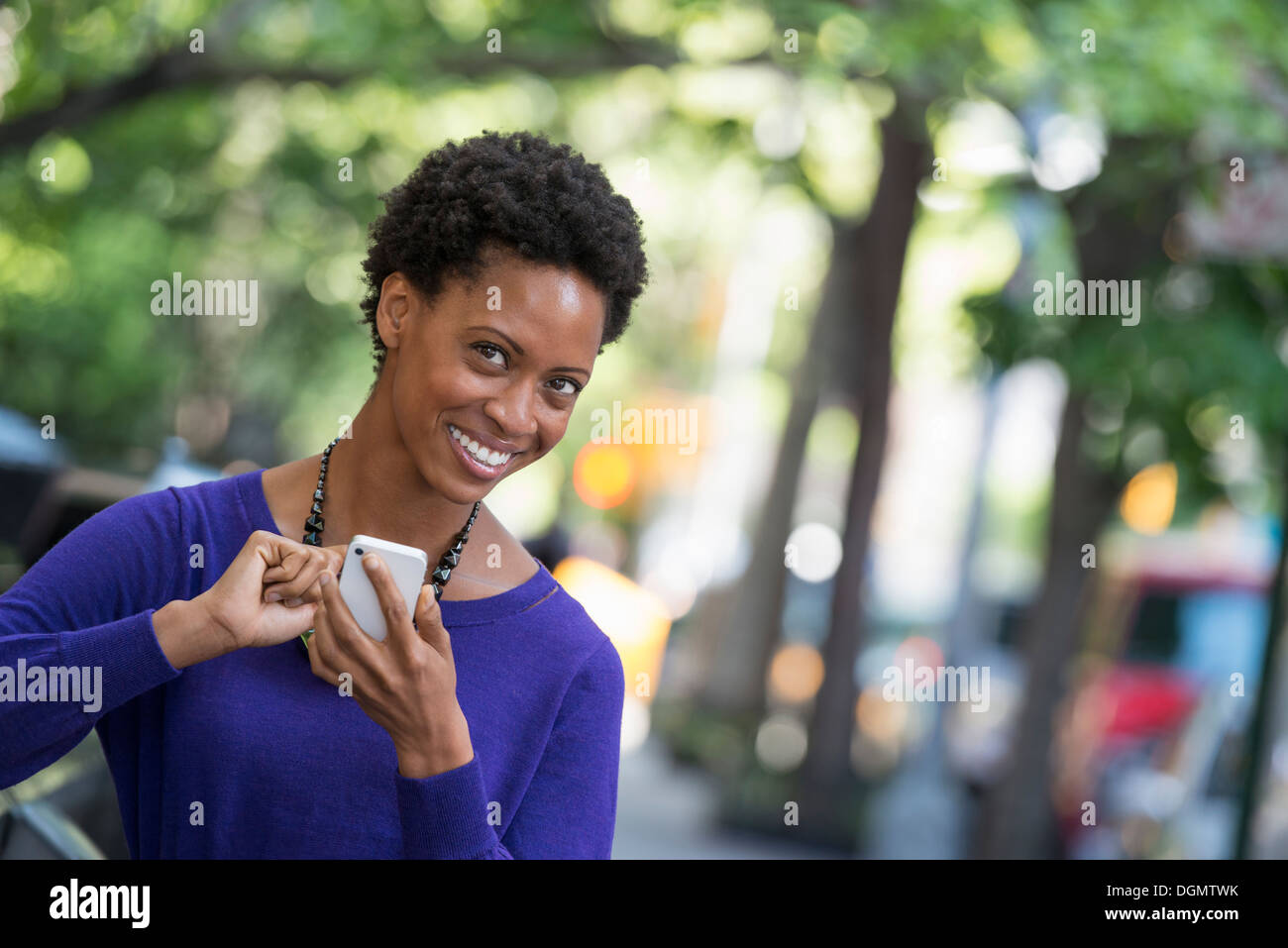 City. A woman in a purple dress checking her smart phone. - Stock Image