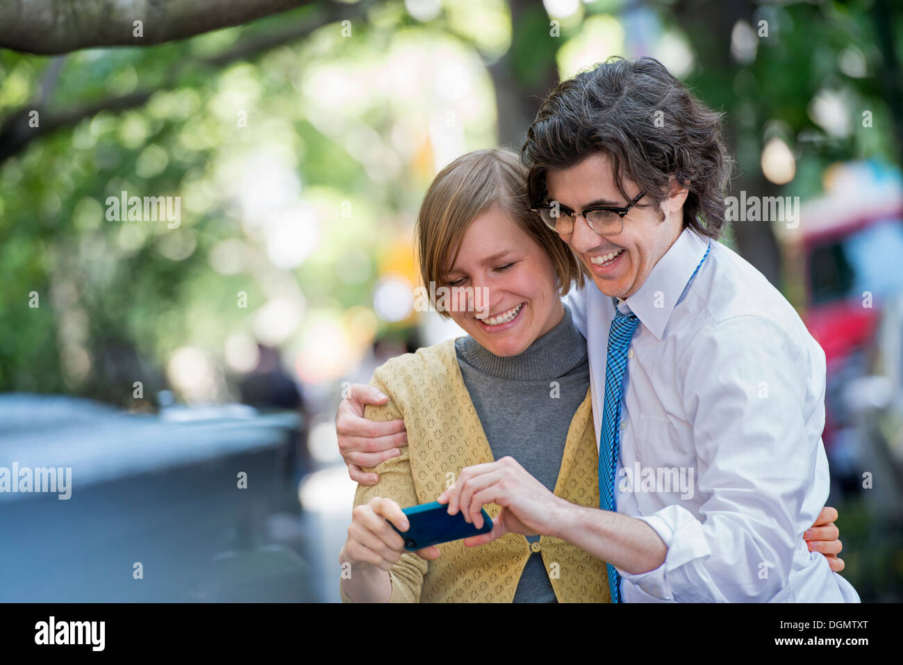 City. Two people, a man and woman outdoors, looking at a smart phone together. - Stock Image