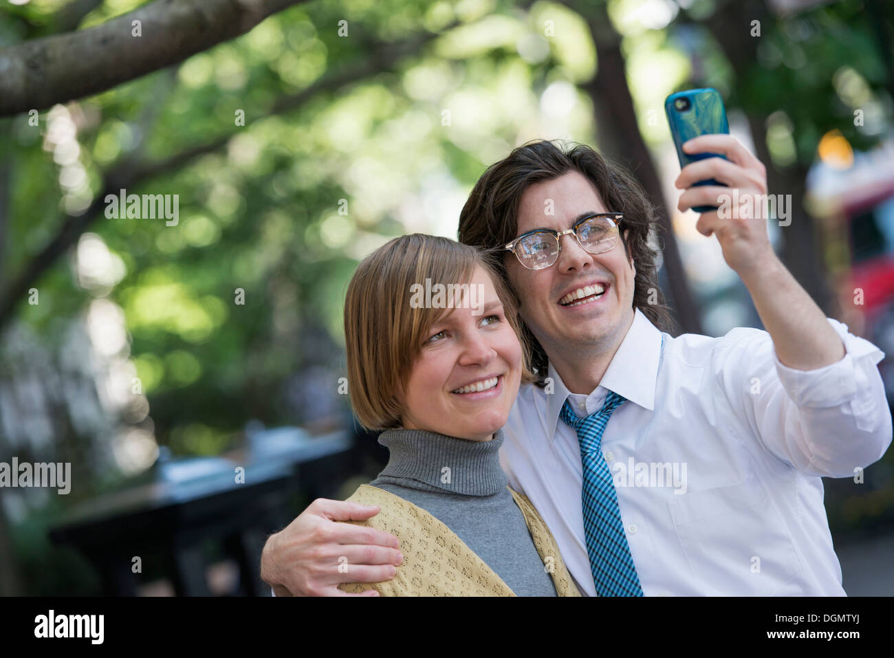 City. Two people, a man and woman outdoors, side by side posing for a photograph using his smart phone. Stock Photo