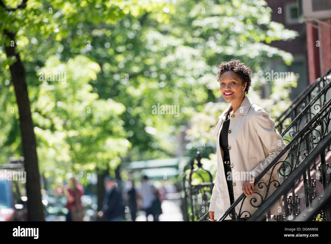 City. A woman walking down steps outside a town house. - Stock Image