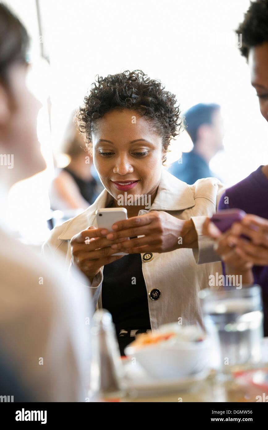 City life. A group of people in a café, checking their smart phones. - Stock Image