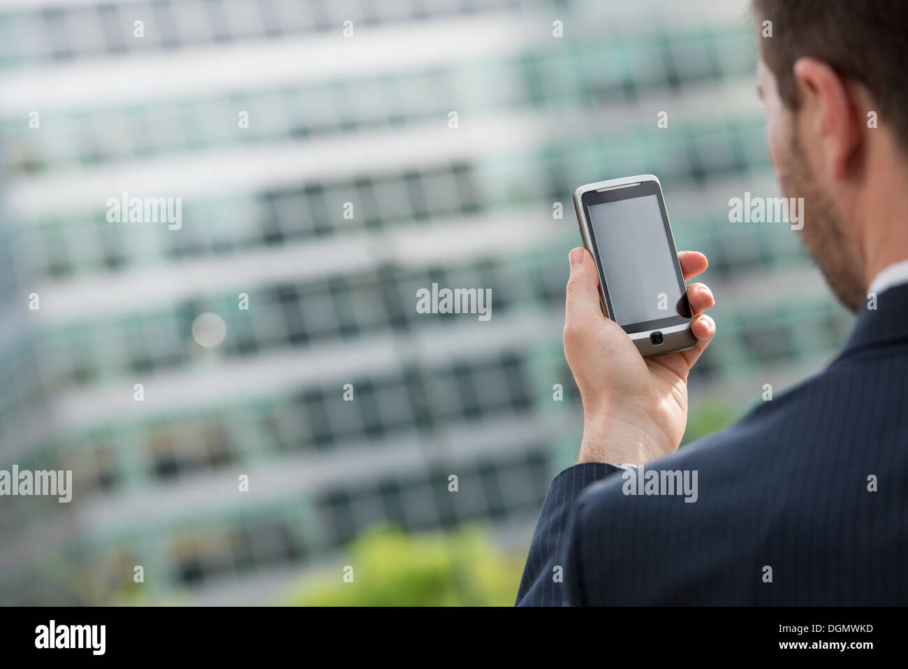City. A man in a business suit checking his messages on his smart phone. - Stock Image