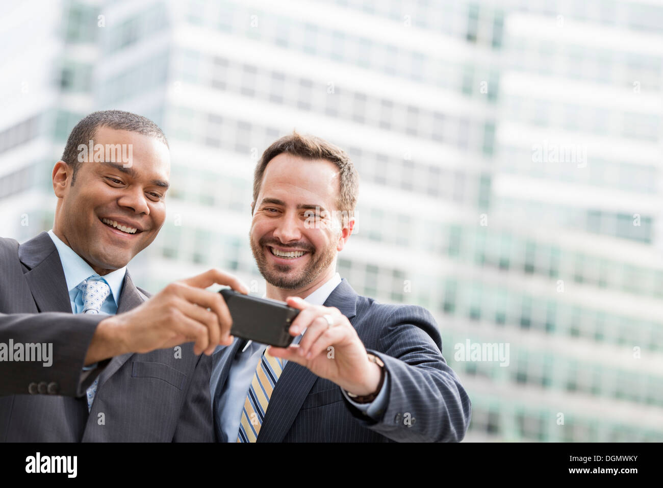 City. Two men in business suits, looking at a smart phone, smiling. - Stock Image