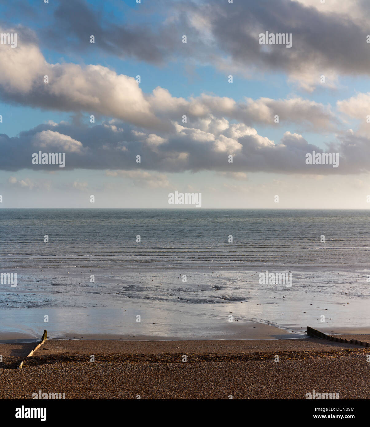 Looking out on a calm sea with late afternoon light reflecting the clouds in the calm water between two groynes Worthing England - Stock Image