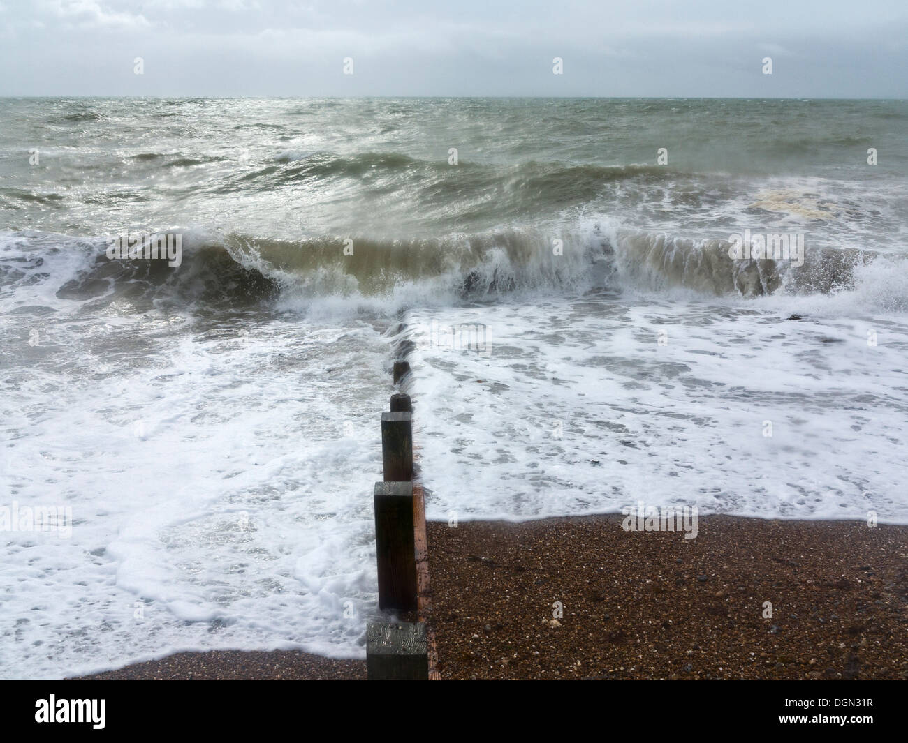 A rough sea breaking on a groyne on a pebble beach with a stormy sky on the horizon, Worthing England - Stock Image