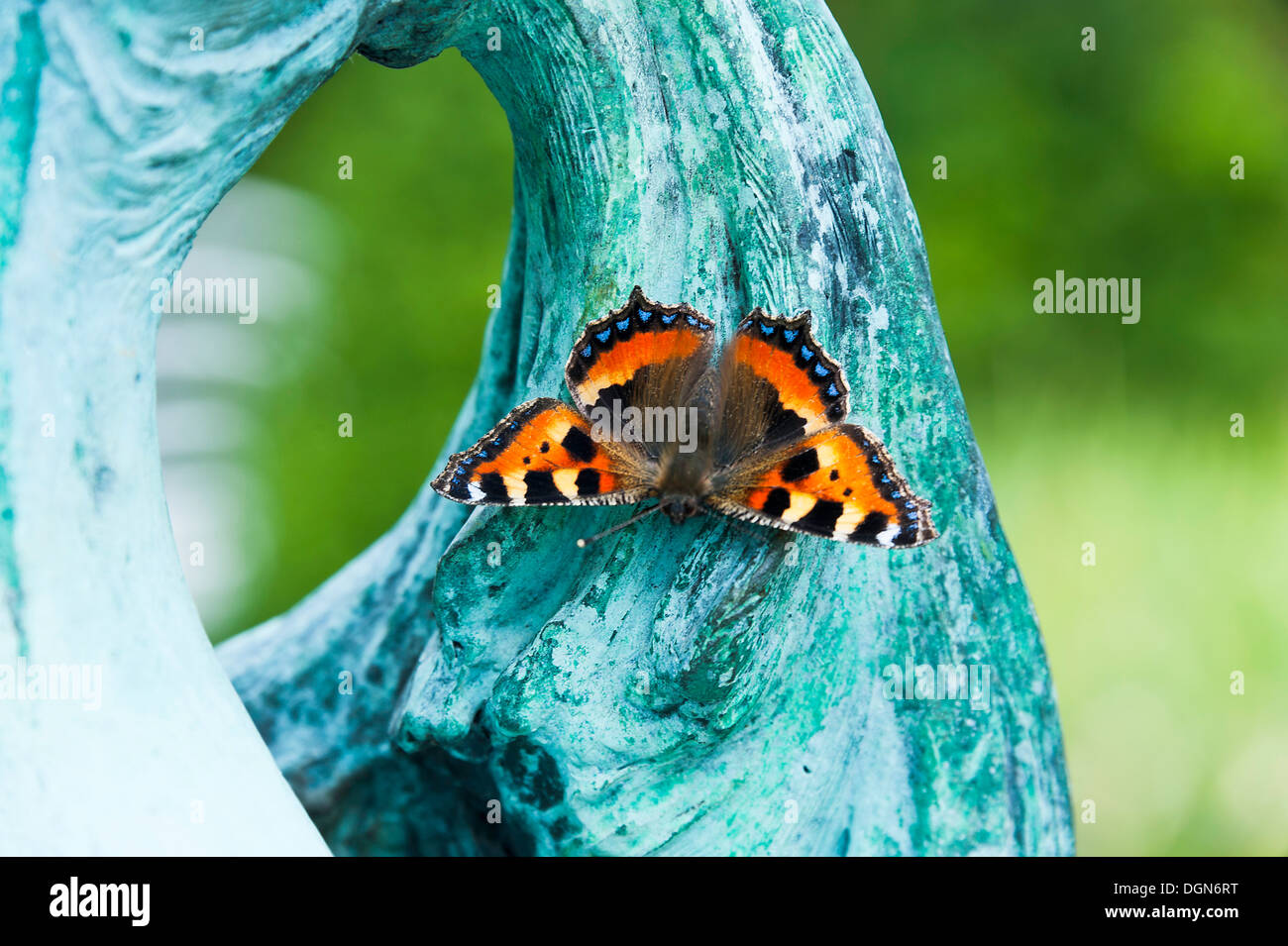 A Small Tortoiseshell Butterfly Resting on a Sculpture at Waterperry Gardens Thame Oxfordshire England United Kingdom UK - Stock Image