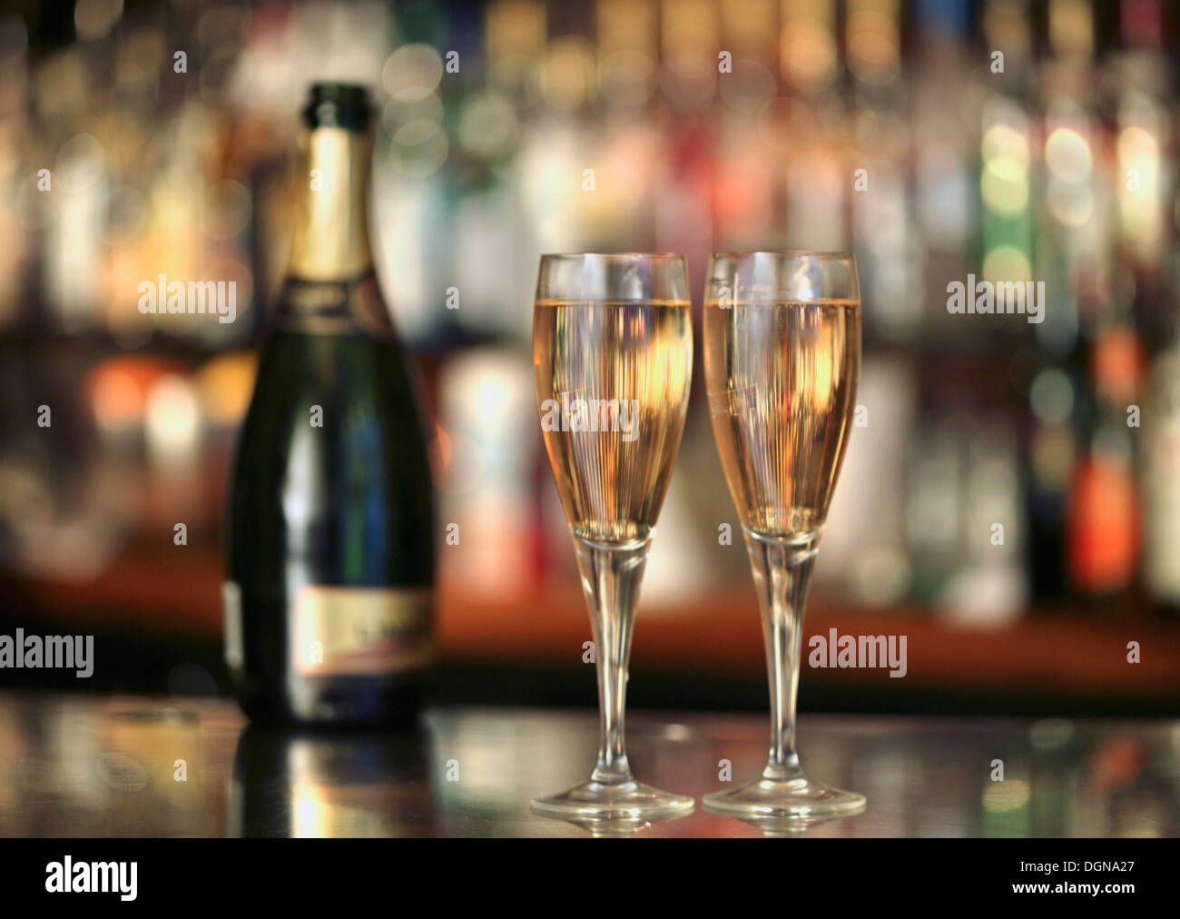 A champagne bottle and two glasses of champagne on a bar - Stock Image