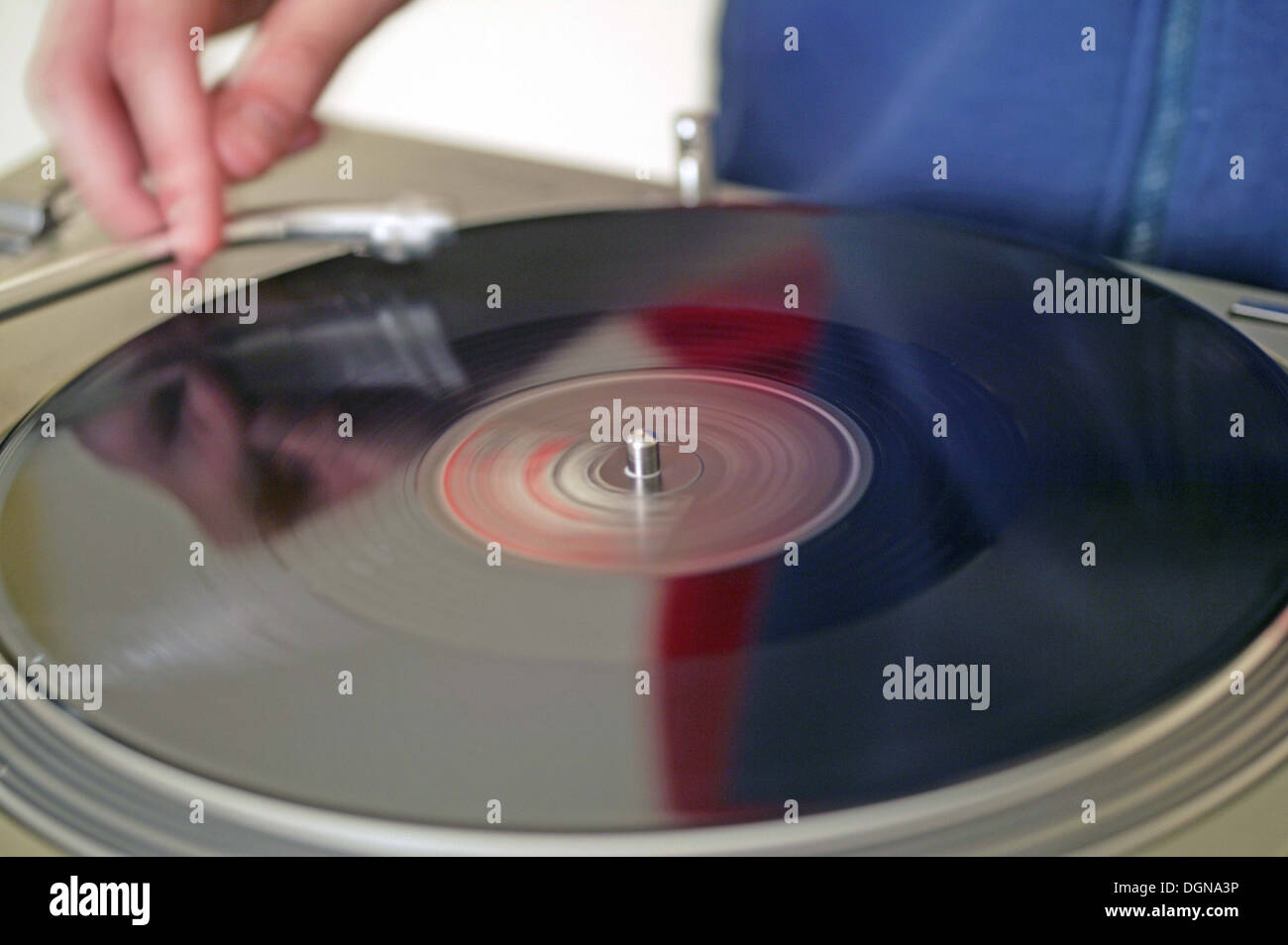 A DJ playing a record on a turntable, close up - Stock Image