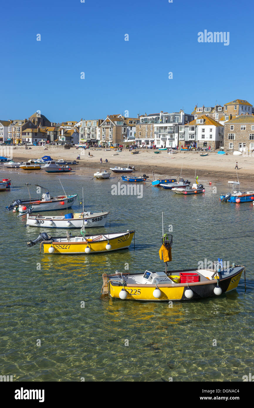 St. Ives harbour shalow clear sea water, fishing boats and beach from the pier. - Stock Image