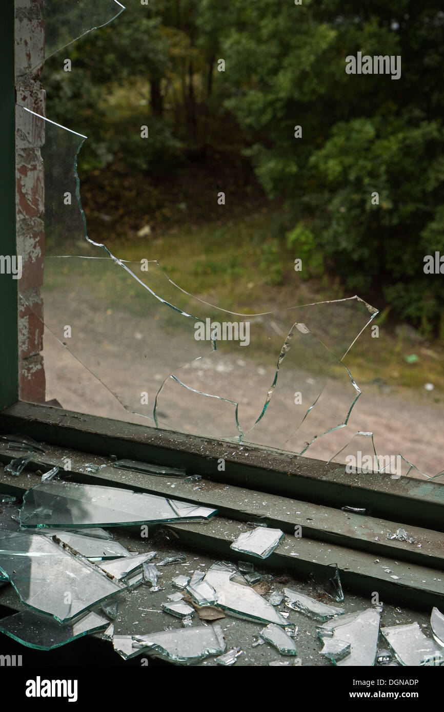 Broken window and pieces of broken glass - Stock Image
