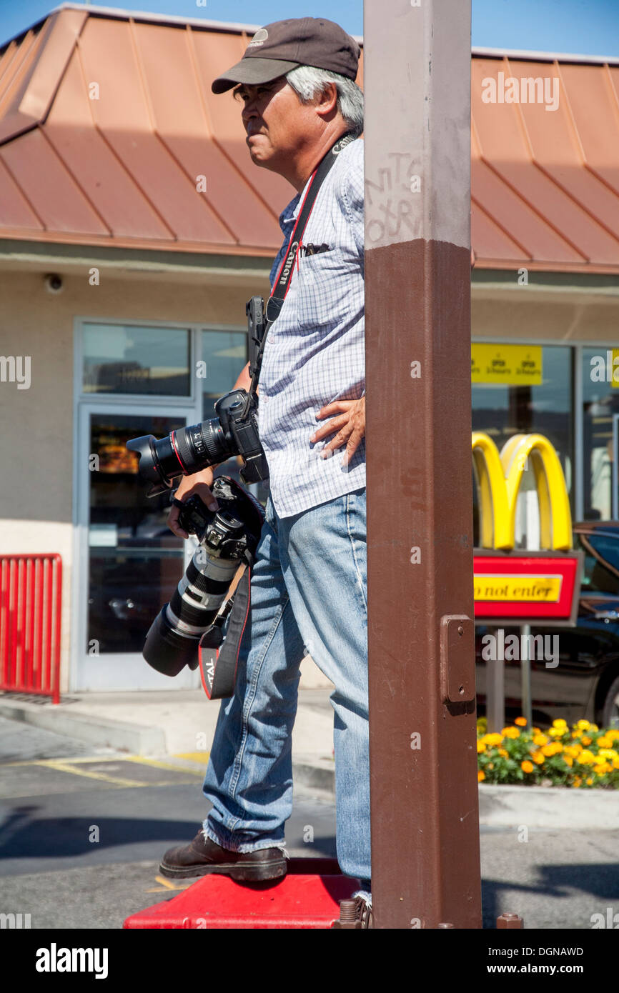 Carrying two digital cameras, Associated Press photographer Nick Ut covers a labor demonstration in a Los Angeles parking lot. - Stock Image
