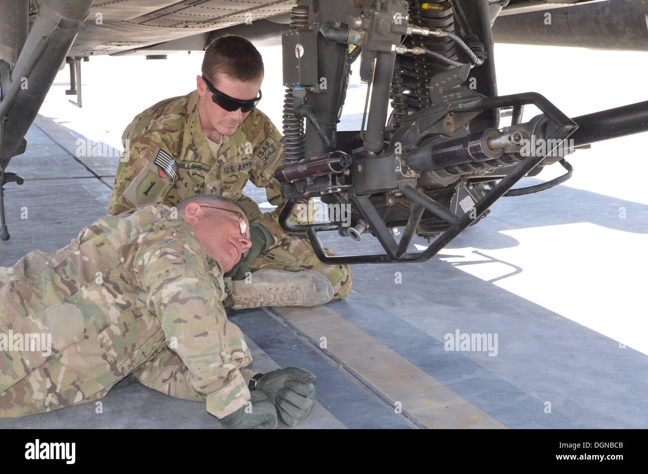 Observing his student, Sgt. Cameron Phillips, an AH-64 Apache armament, electrical and avionics systems maintainer with Task Force Guardians, 1st Combat Aviation Brigade, 1st Infantry Division, shows Maj. Gen. Paul LaCamera, Regional Command-South and 4th - Stock Image