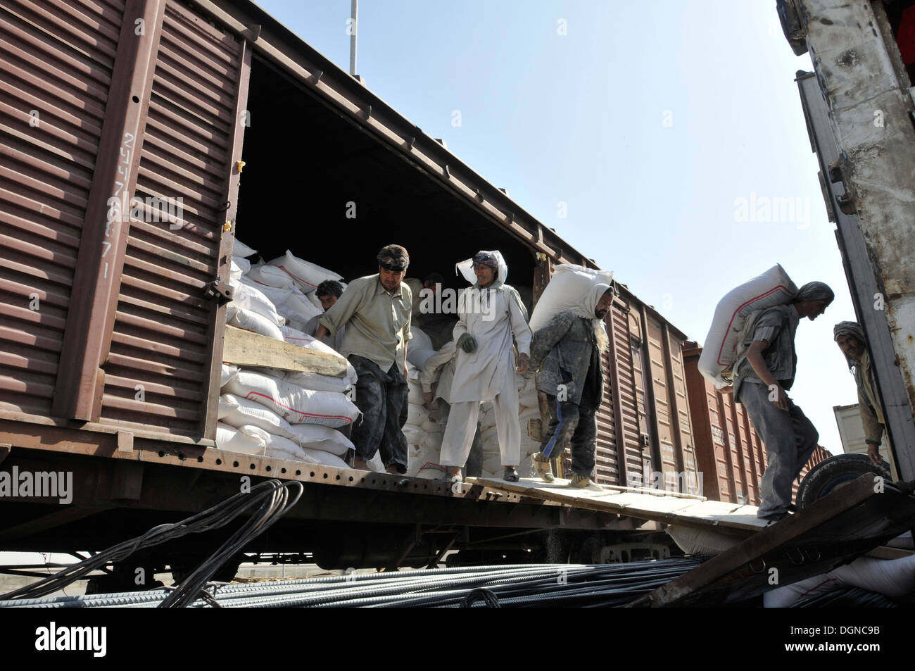 Rail Port 4, Niababad, Afghan laborers begin the manually intensive process of offloading 100 pound plus bags of baking flour from a boxcar onto waiting semi trucks for shipment to Afghan markets. The flour was imported through Uzbekistan. - Stock Image