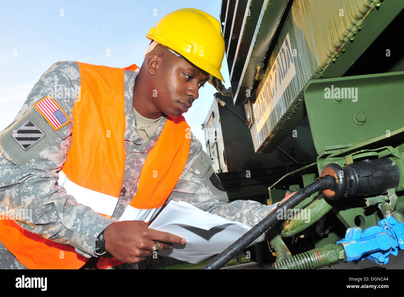 Staff Sgt. Tyler P. Jackson, the transportation movement and installation staging area supervisor with the 21st Theater Sustainment Command and a native of Queens, N.Y., inspects a vehicle belonging to the 5th Battalion, 7th Air Defense Artillery at Rhine - Stock Image