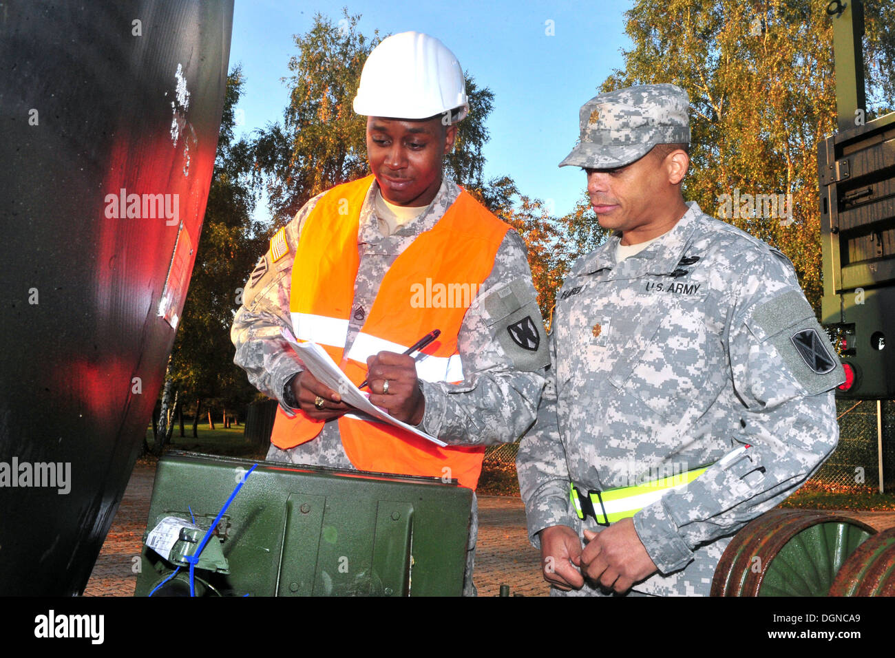 Staff Sgt. Tyler P. Jackson, (left) the transportation movement and installation staging area supervisor with the 21st Theater Sustainment Command and a native of Queens, N.Y., reviews a piece of equipment's serial number with Maj. Ernest J. Harrell, the - Stock Image
