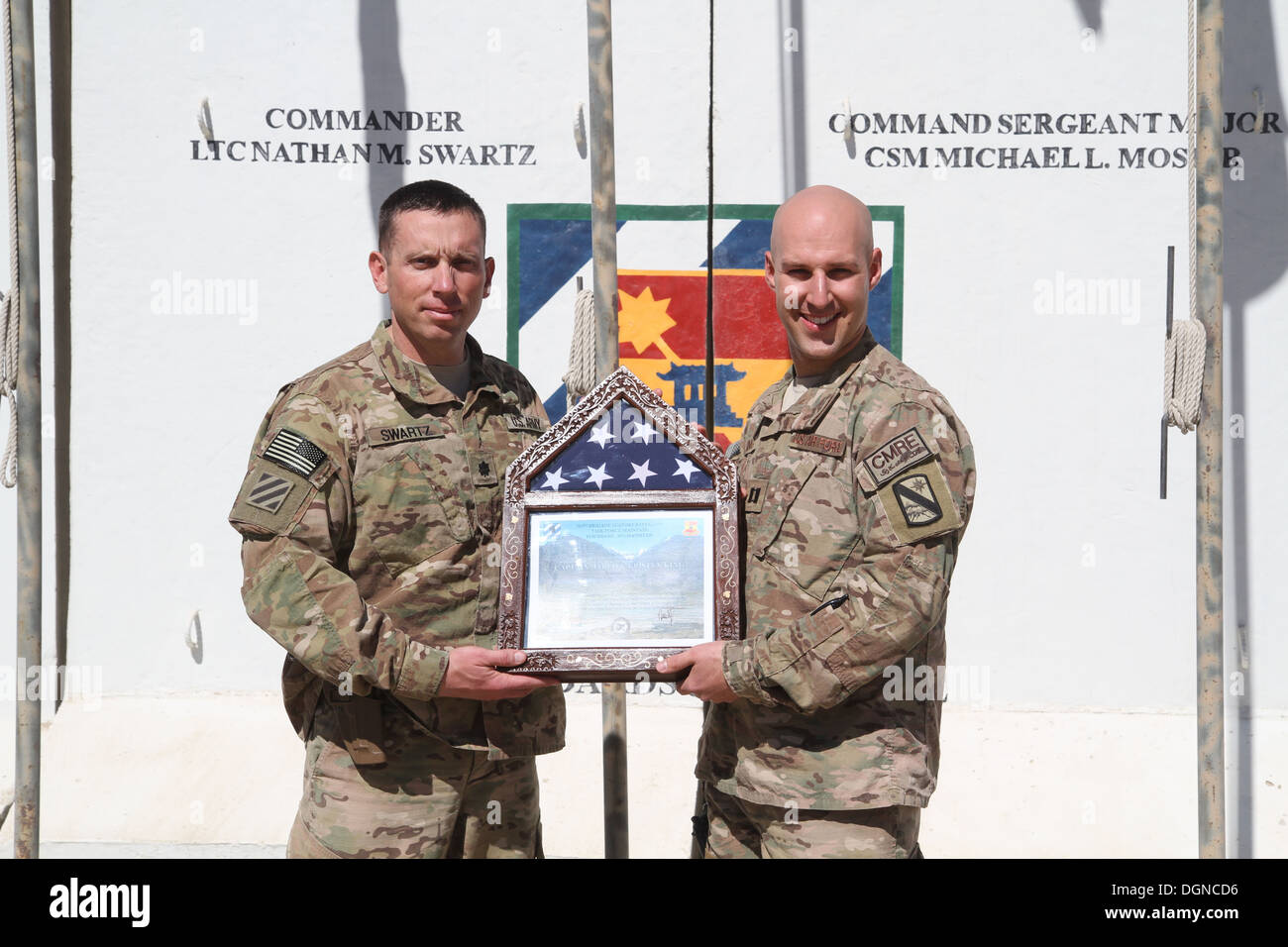 U.S. Air Force Capt. Jared King (right), a Forrest Hill, Md., native and cyber warfare operator attached to Central Command's Materiel Recovery Element, receives a flag and certificate from U.S. Army Lt. Col. Nathan Swartz, a native of Tullahoma, Tenn., a - Stock Image