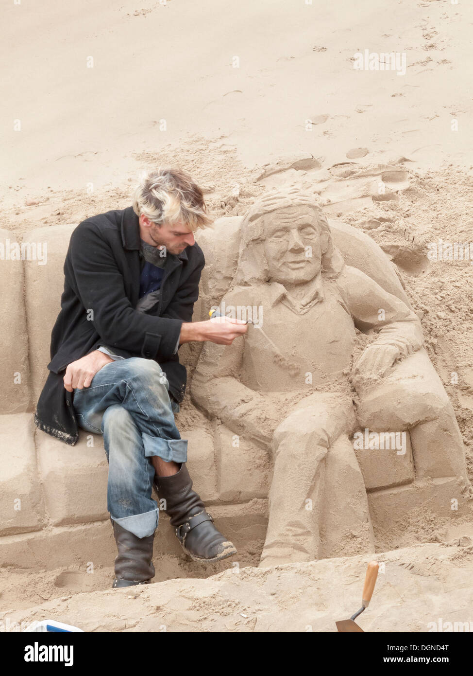 Sculptor concentrating on creating sand sculpture of a man reclining on a sofa, on River Thames South Bank, London, UK for tips - Stock Image