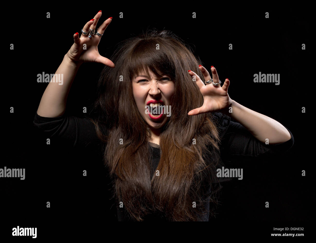 Woman throwing a temper tantrum screaming in anger and clawing the air with her hands on a dark background - Stock Image