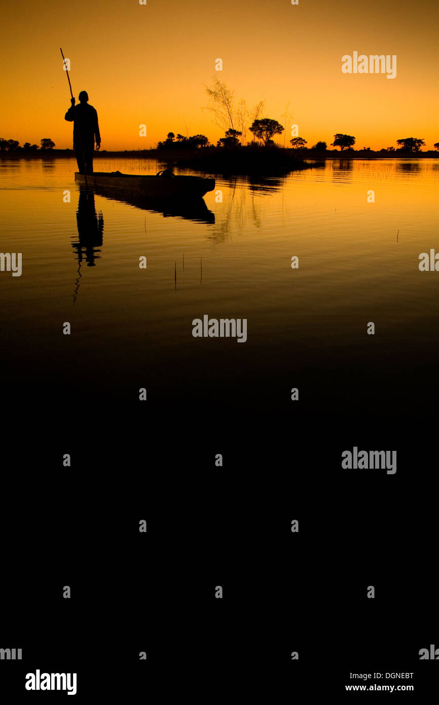 A Okavango Delta poler is a silhouette at dusk in his Mokoro - Stock Image