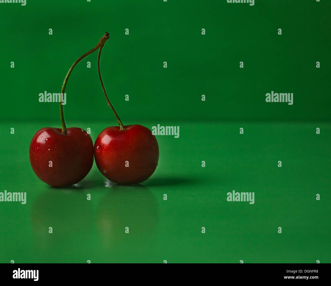 Red cherries on green background - Stock Image