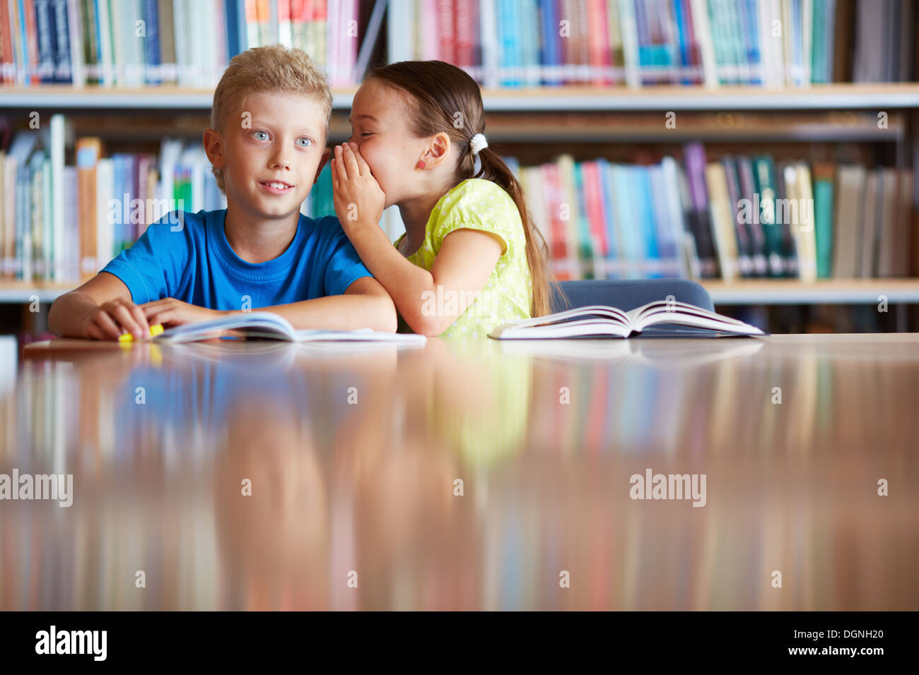 Portrait of cute schoolgirl whispering something to her classmate in library - Stock Image