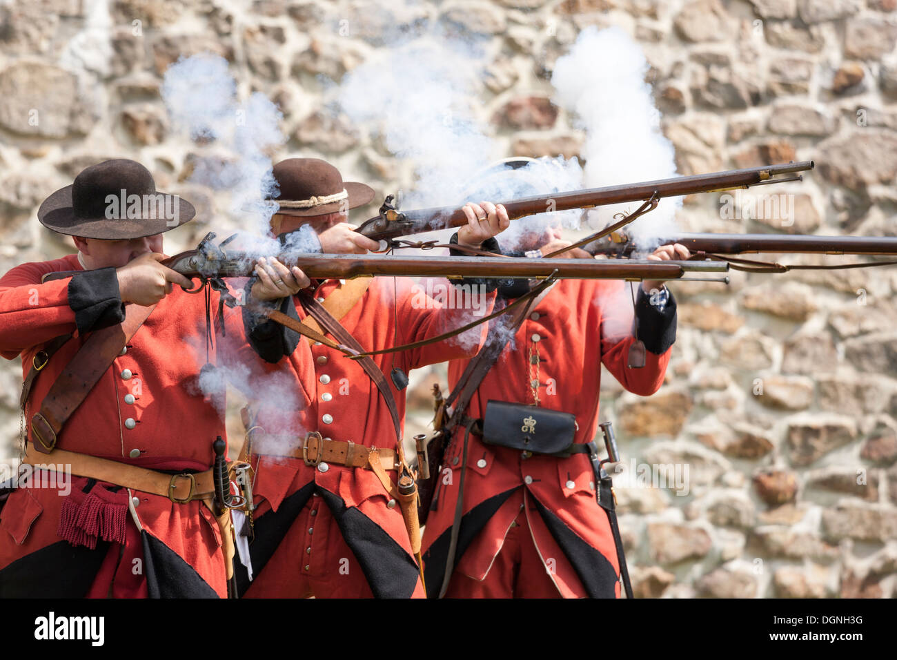 Soldiers firing flintlock muskets in re-enactment French & Indian American Revolution Revolutionary War of Independence - Stock Image