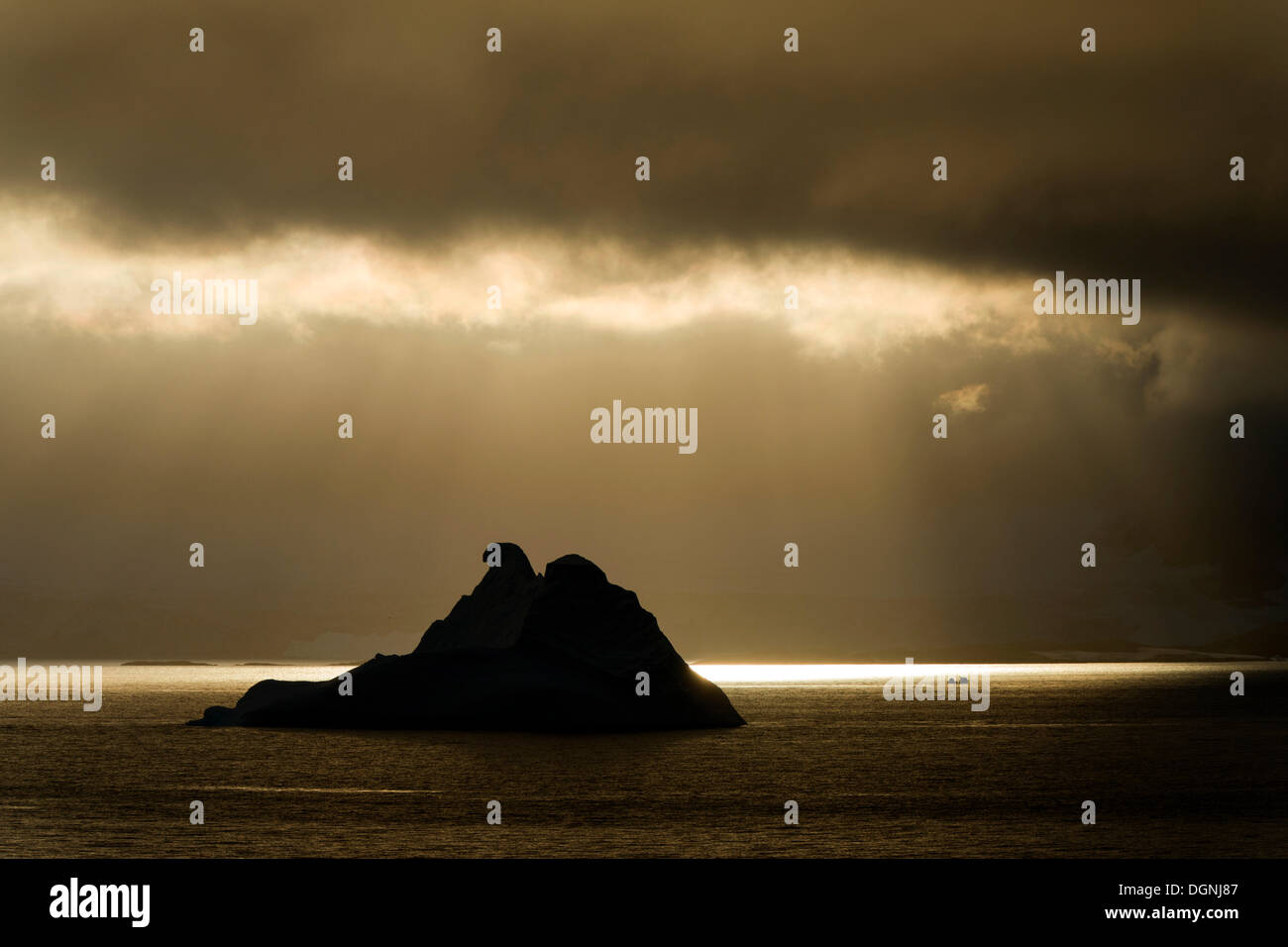 Sunlight shining through a hole in the clouds, silhouette of an iceberg at the front, Errera Channel, Arctowski Stock Photo