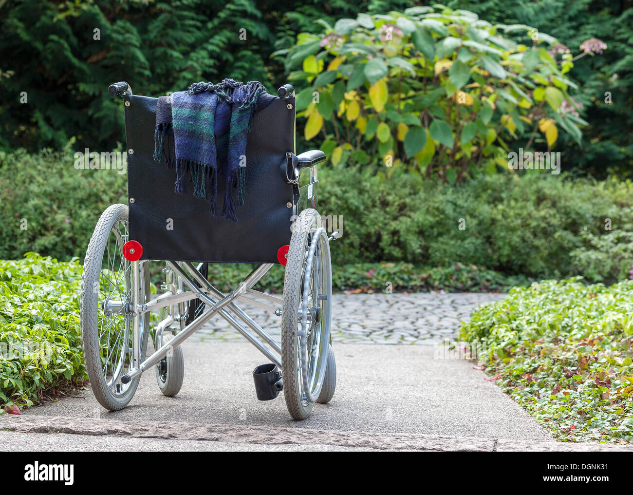 Abandoned wheelchair in a green area, Berlin, Germany Stock Photo