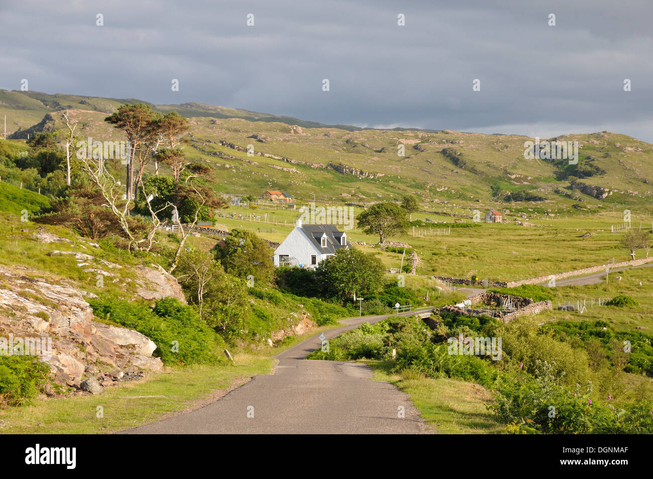 Narrow street in a sparsely populated coastal landscape on the coast of the Atlantic Ocean, Northern Highlands, Highlands - Stock Image