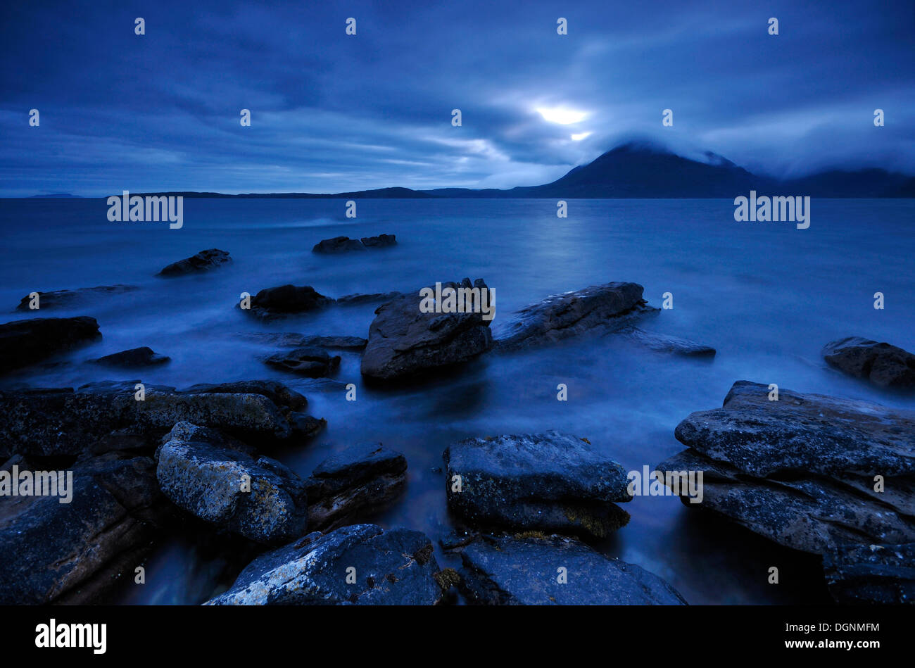 Mountains shrouded with clouds, blue hour on a rocky seashore, Elgol, Isle of Skye, Scotland, United Kingdom - Stock Image