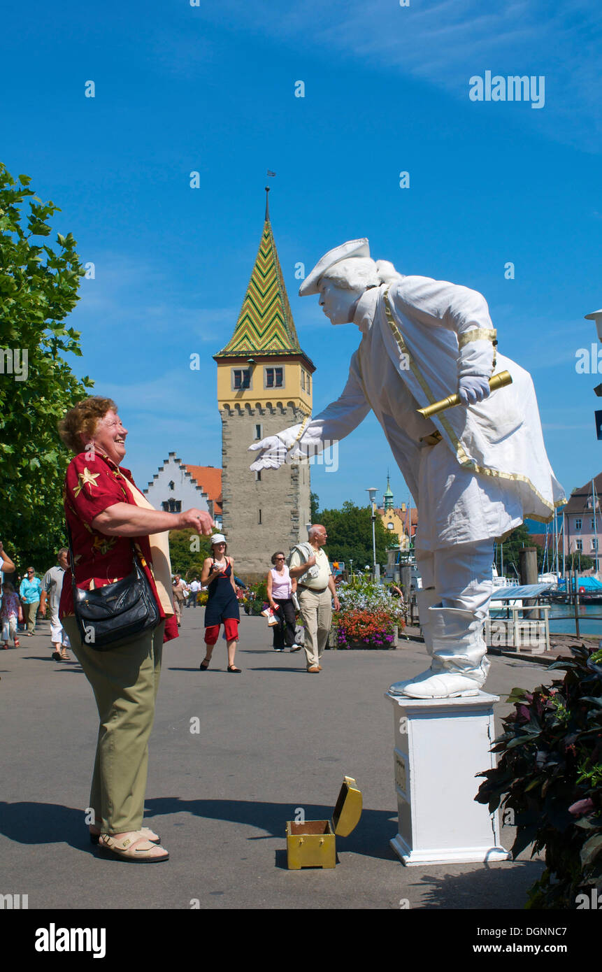 Street performer, living statue in front of the Mangturm tower at the harbor, Lindau, Lake Constance, Bavaria Stock Photo