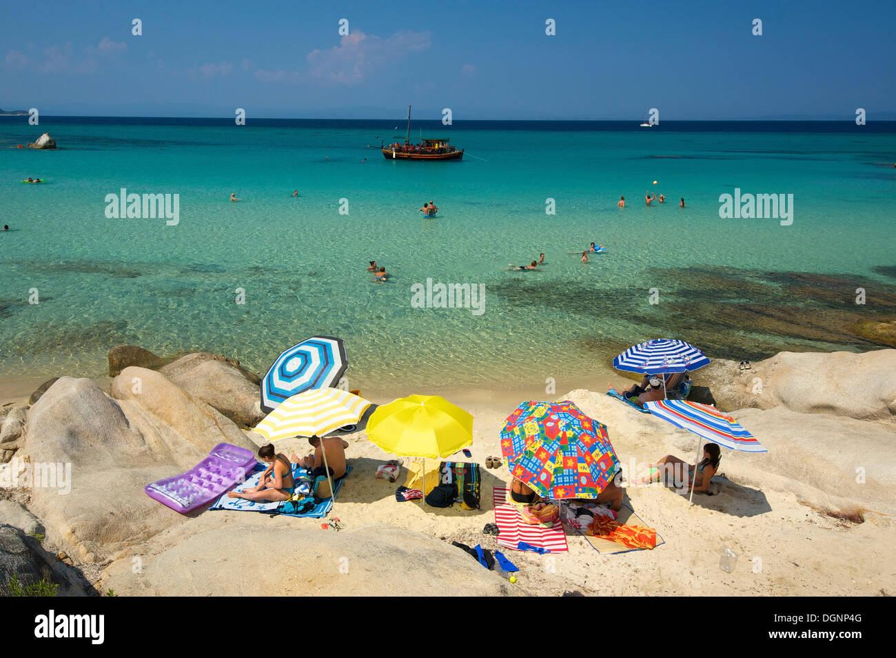Tourists with parasols at the beach of Portokali, Kavourotypes, Sithonia, Chalkidiki or Halkidiki, Greece, Europe Stock Photo