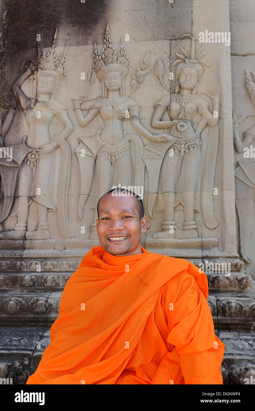 Buddhist monk in the centre of Angkor Wat sitting in front of a relief depicting Apsara from Hindu mythology, Cambodia Stock Photo