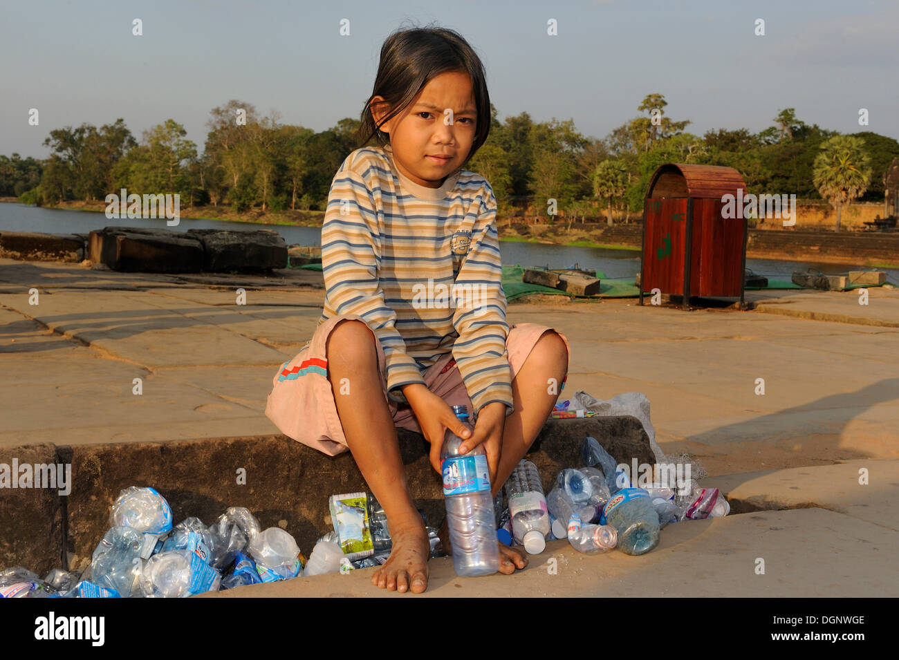 Girl collecting empty water bottles left by tourists and squashing them to earn money, in front of the Angkor Wat, Siam Reap - Stock Image