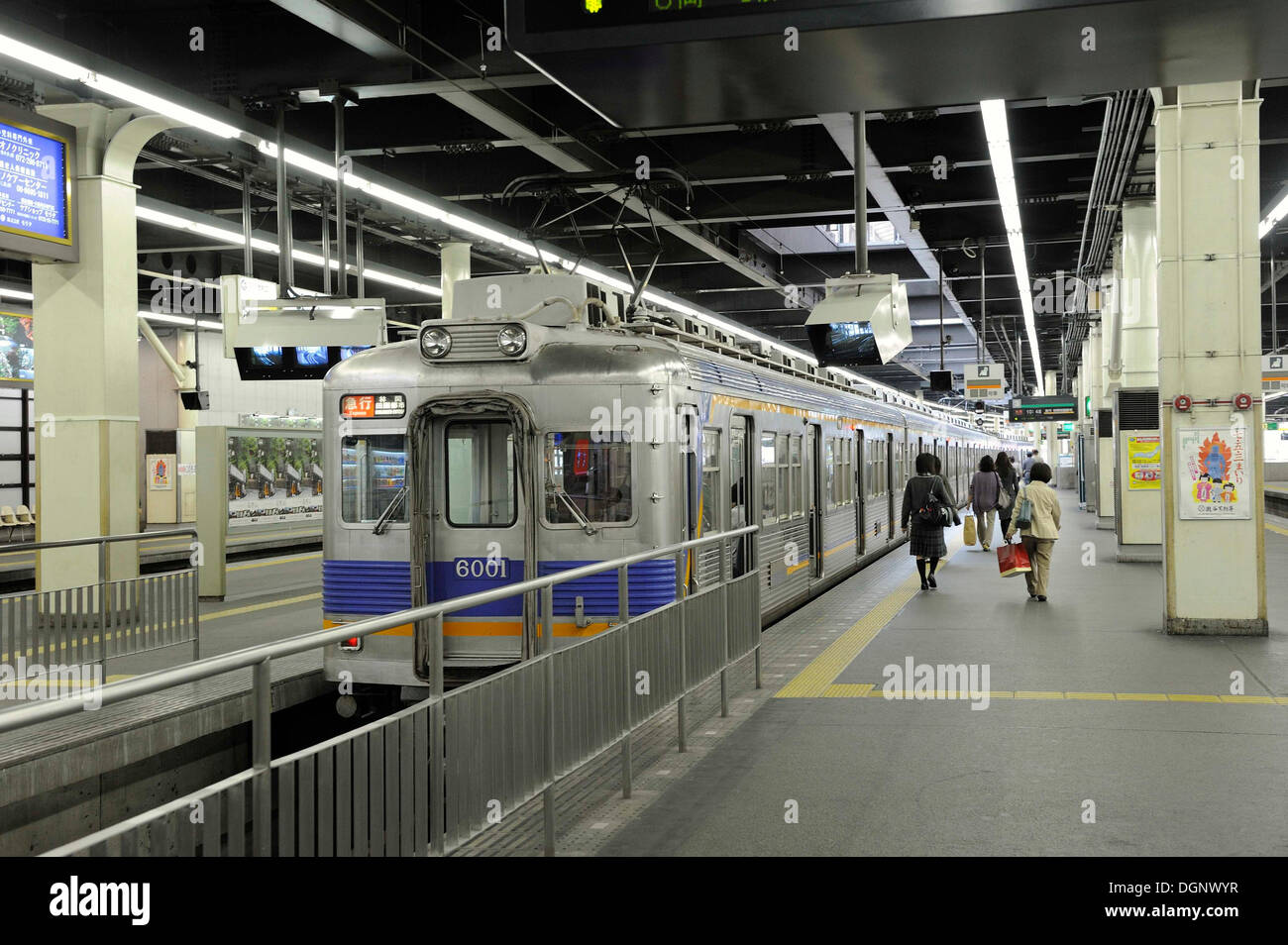 Train from the Nankai Line at the station on a platform with a yellow guide strip for the visually impaired on the ground and - Stock Image