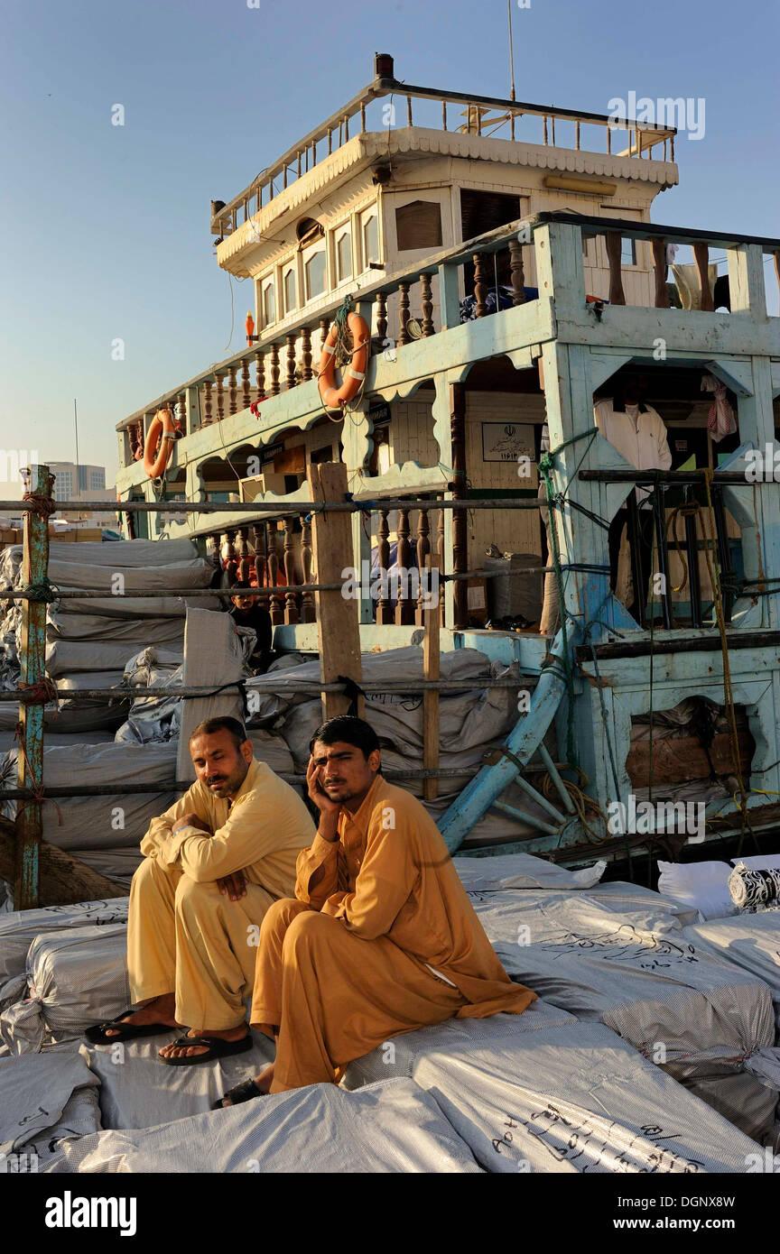 Dockers sitting on sacks on a dhow, Daira, Dubai, Emirate of Dubai, United Arab Emirates - Stock Image