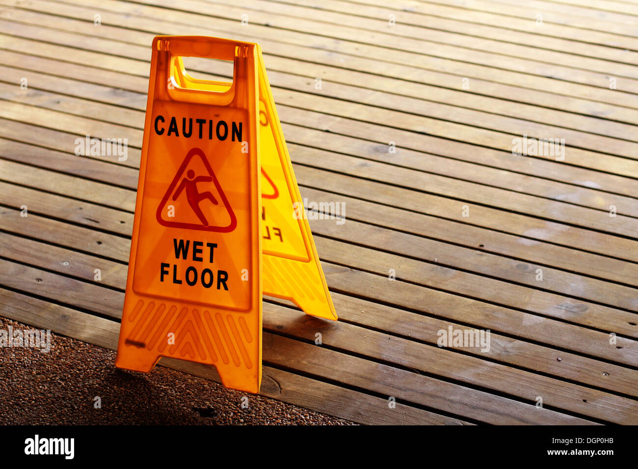 A wet floor sign on a wood deck - Stock Image