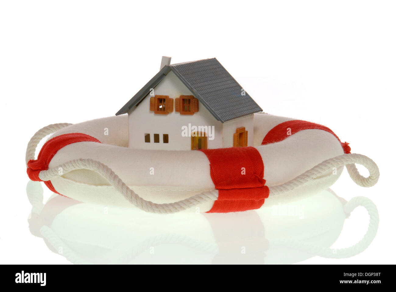 Miniature house in a life saver, symbolic image for saving homes - Stock Image