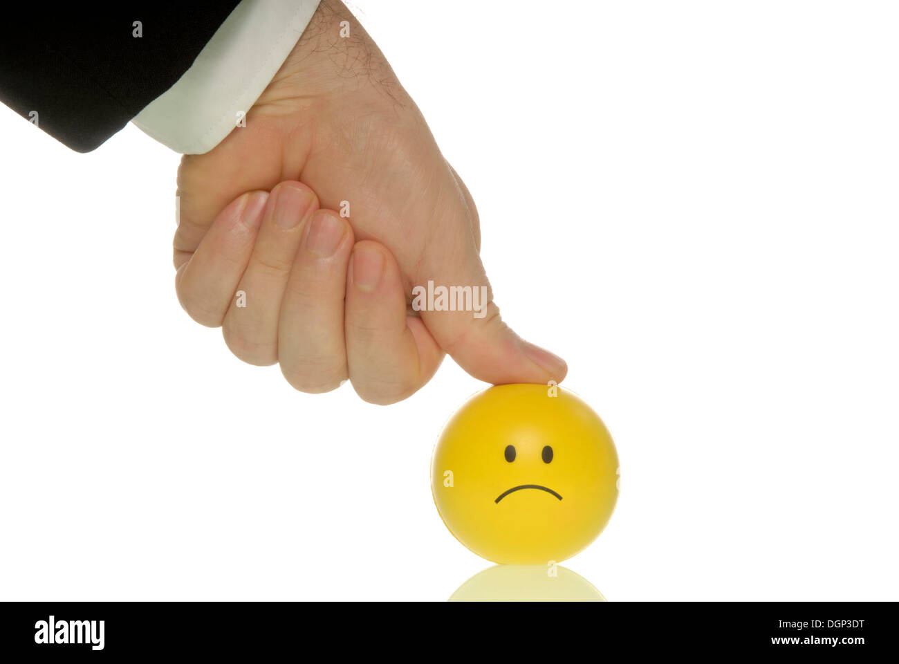 Businessman pressing his thumb down on a smiley, symbolic image for pressure to perform - Stock Image