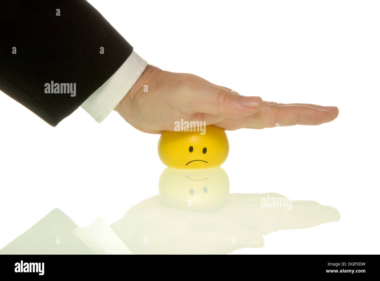Businessman pressing his palm down on a smiley, symbolic image for pressure to perform - Stock Image
