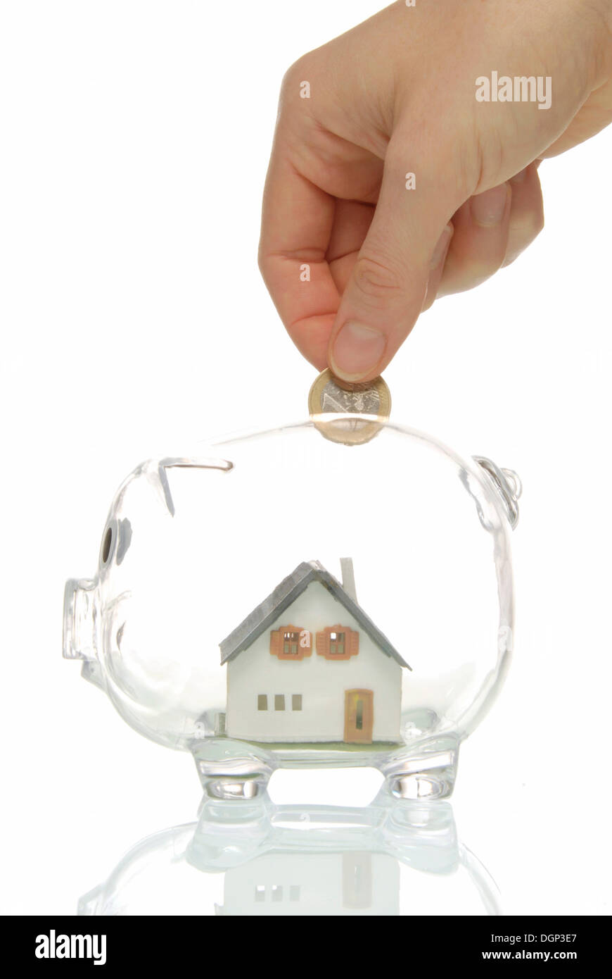 Hand putting coin into piggy bank with a house, symbolic image for building society savings - Stock Image