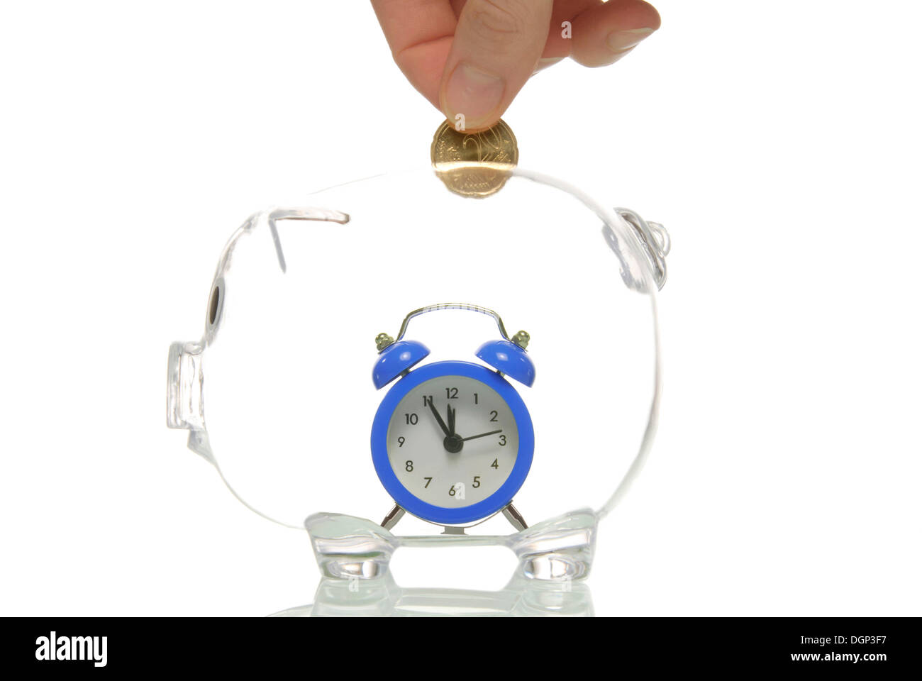Piggy bank with an alarm clock showing 5 to 12 - Stock Image