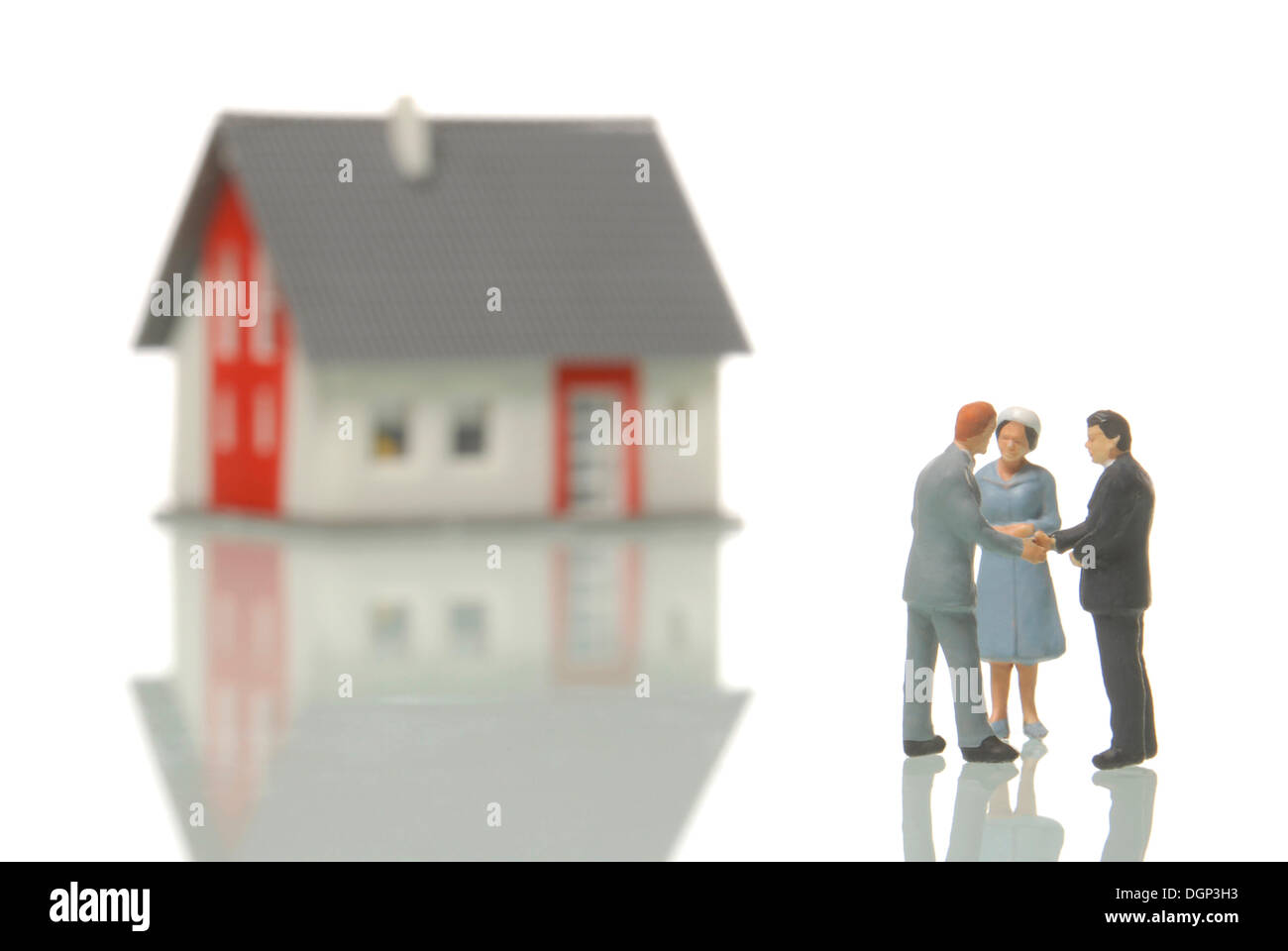 Couple buying a house from a realtor, figurines, a blurred house in the back, symbolic image for the real estate market Stock Photo
