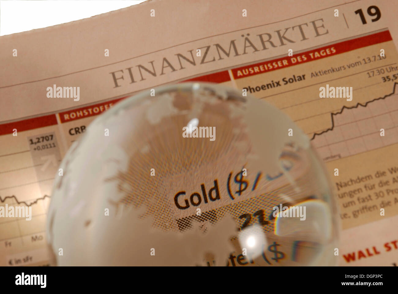 Glass globe on business newspaper, lettering 'gold - Stock Image