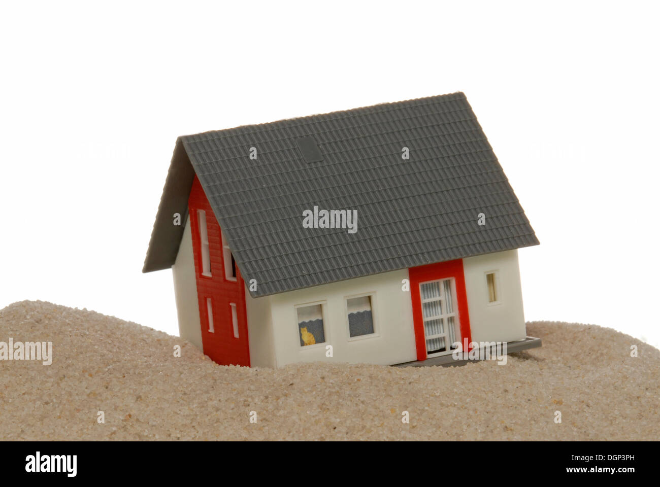 Miniature house built on sand - Stock Image