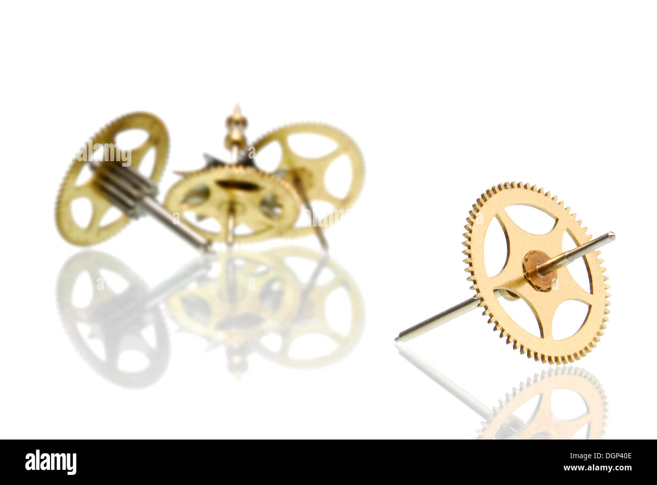 Gears or cog wheels, one at the front in focus, three behind out of focus - Stock Image