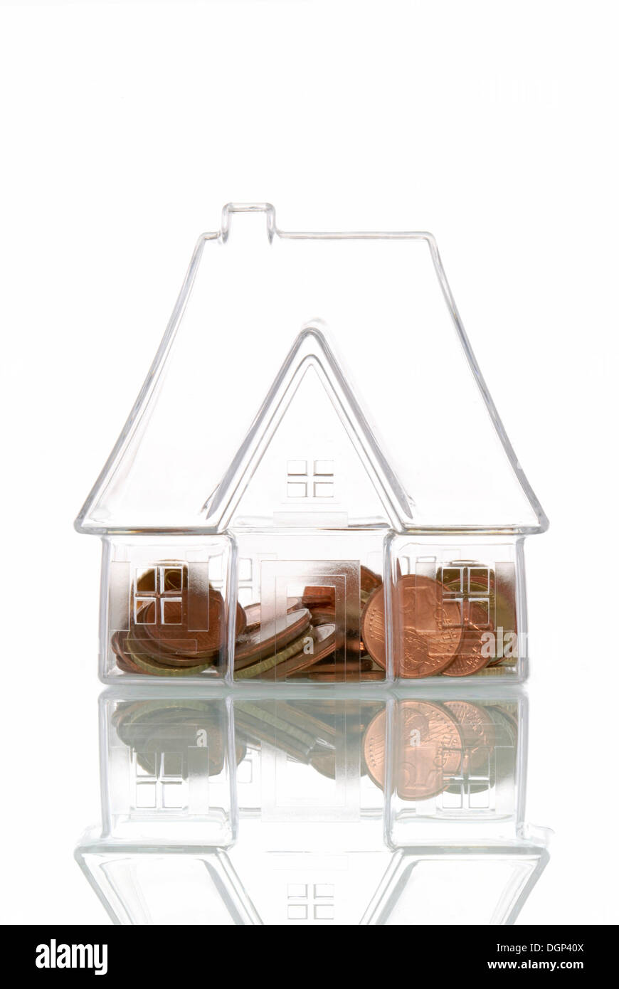Transparent house with coins, symbolic image for transparency in the real estate market, house building costs - Stock Image