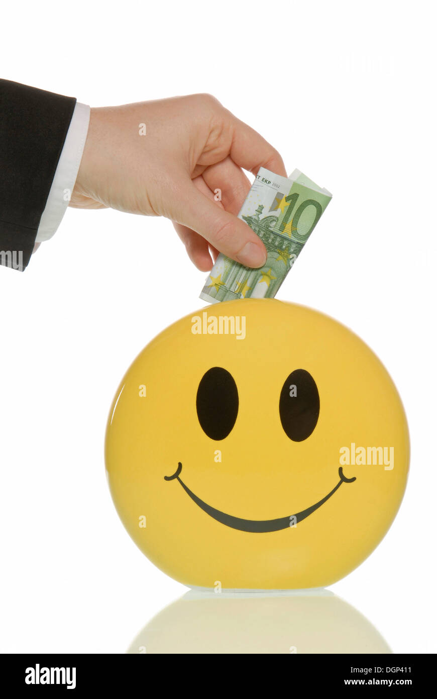 Business man putting a 100-euro note in a smiley piggy bank - Stock Image